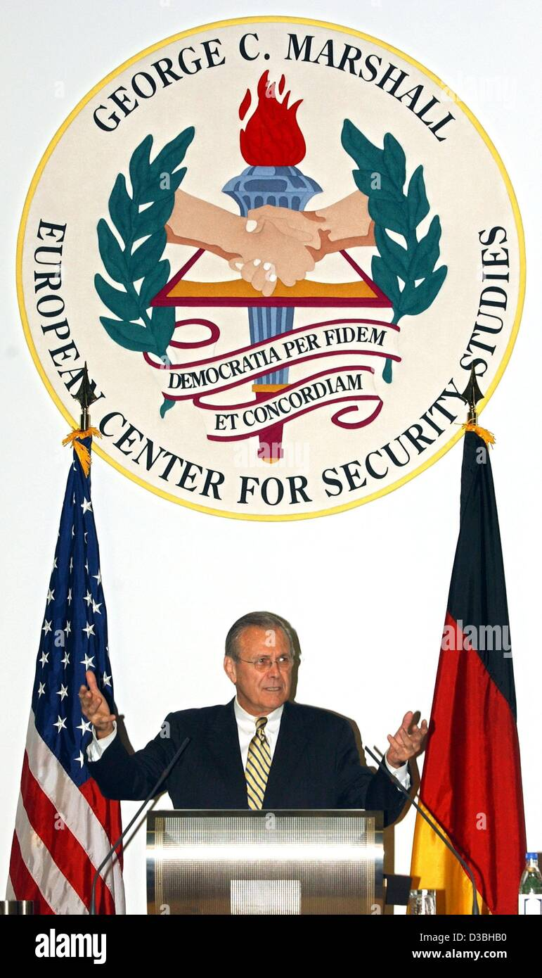 (dpa) - US Defence Minister Donald Rumsfeld is gesturing between the flags of Germany and the USA and the logo of - Stock Image