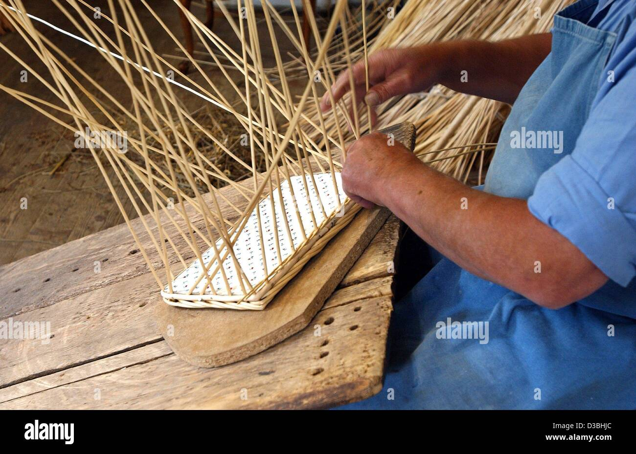 (dpa) - Basket maker Rudolf Ammann works on a basket with a wooden base in his workshop in Oberstdorf, Germany, - Stock Image