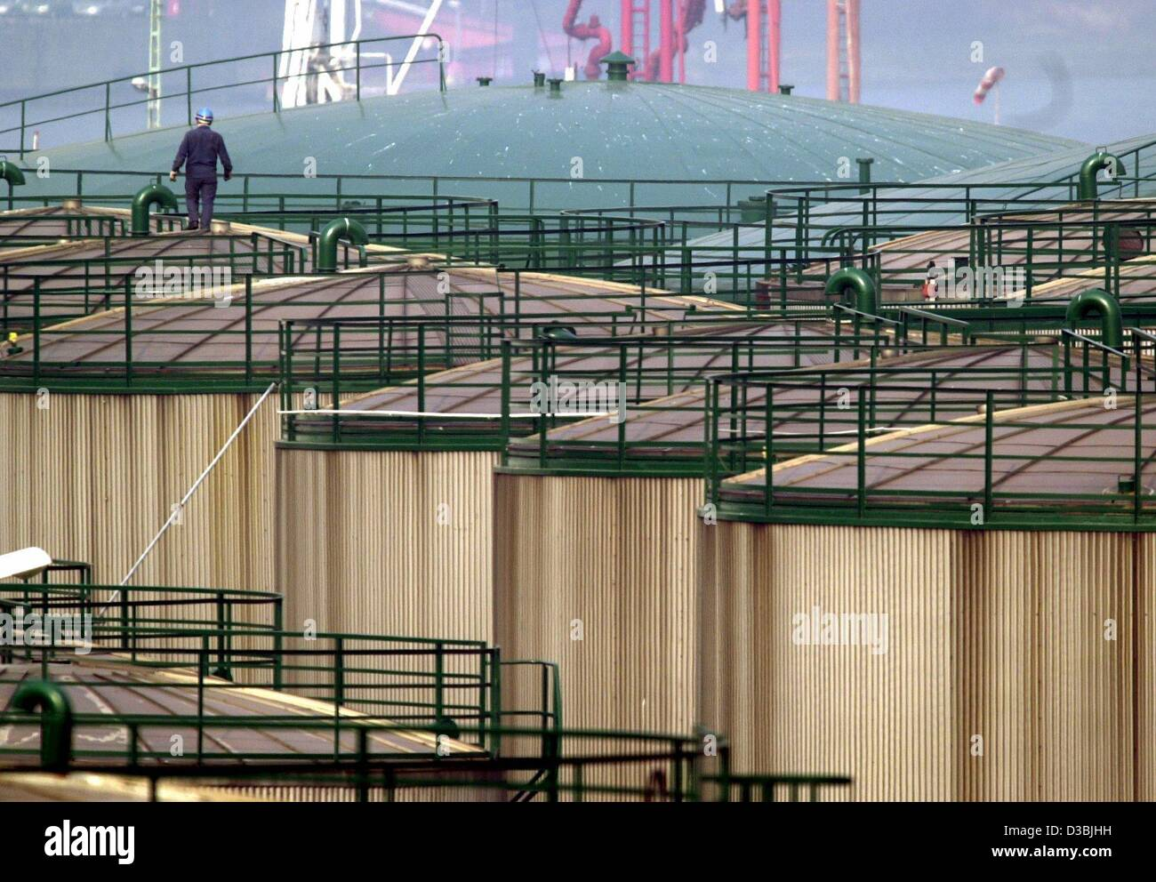 (dpa) - A worker walks across a giant tank filled with petrol and crude oil on the premises of the oil tank depot - Stock Image