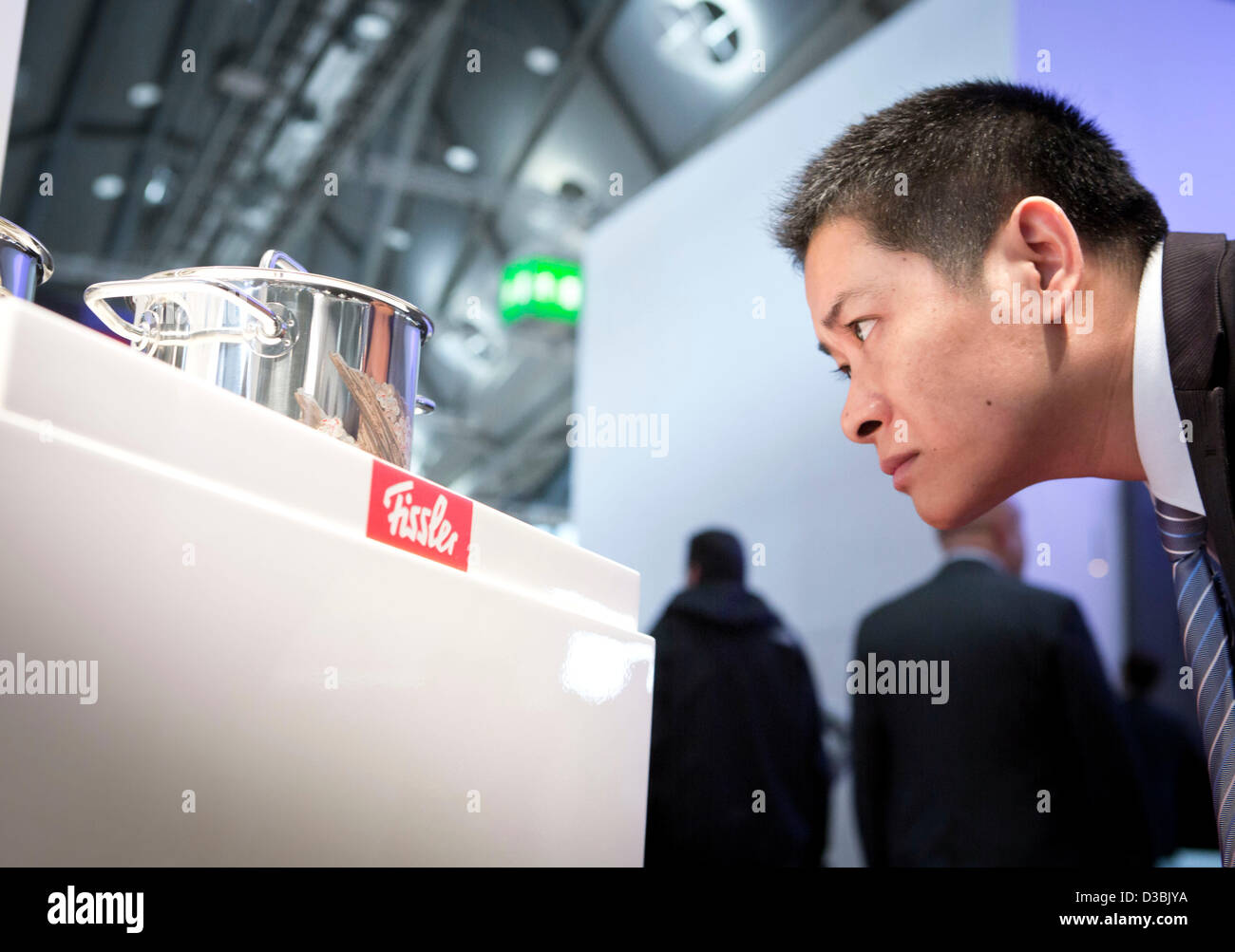 A Chinese visitor looks at a Fissler 'AsianArtEdition' pot at the company's stand at the - Stock Image