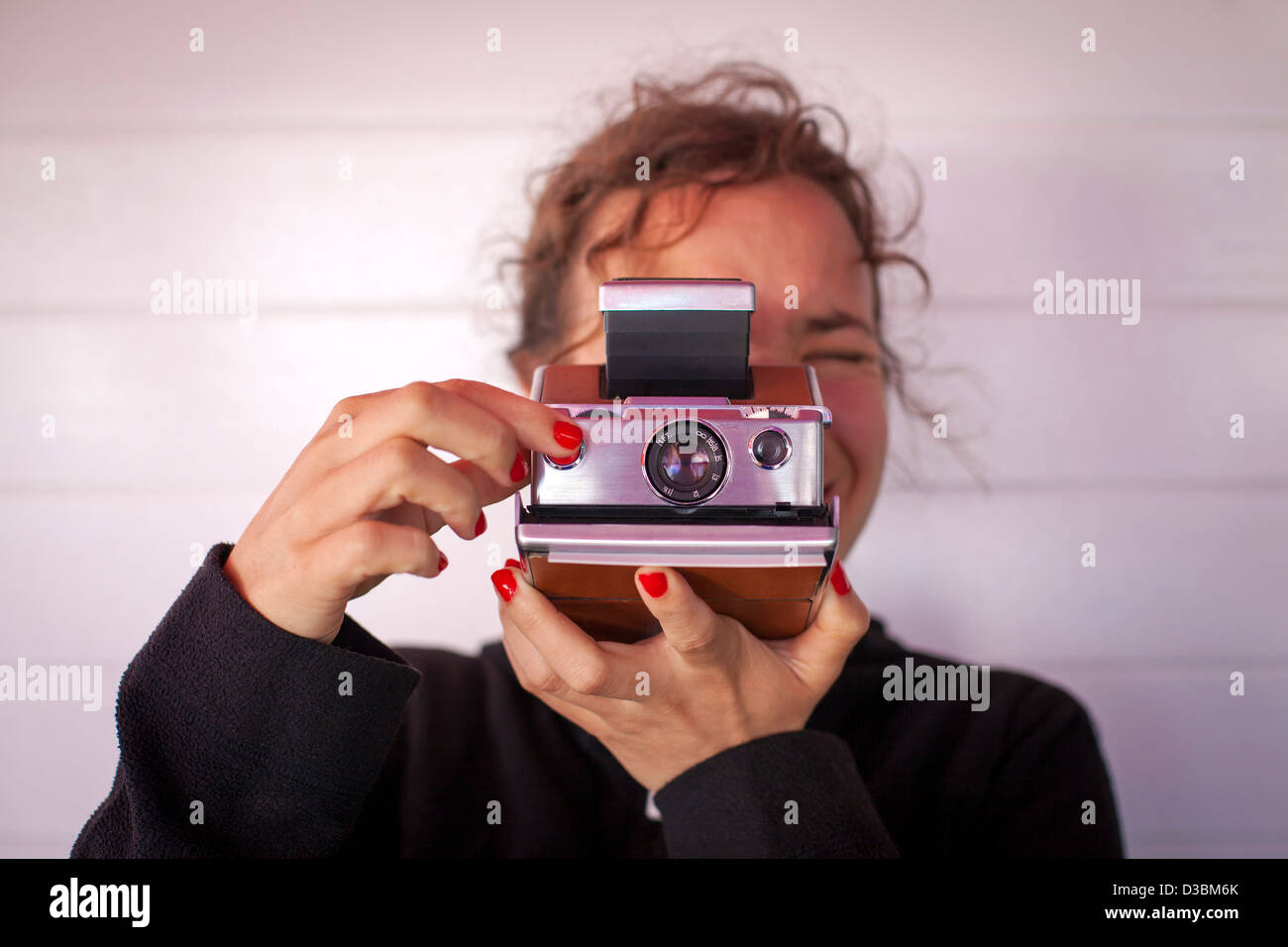 Girl taking a photograph with a Polaroid camera. - Stock Image