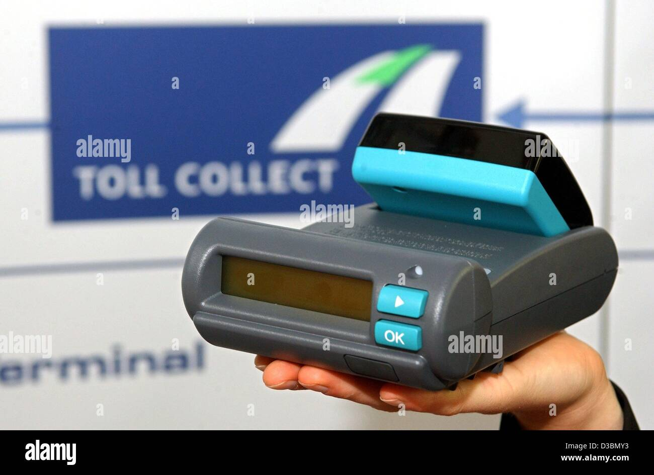 (dpa) - A device for the acquisition of data of the truck toll fees is seen in front of the logo of the comany Toll - Stock Image