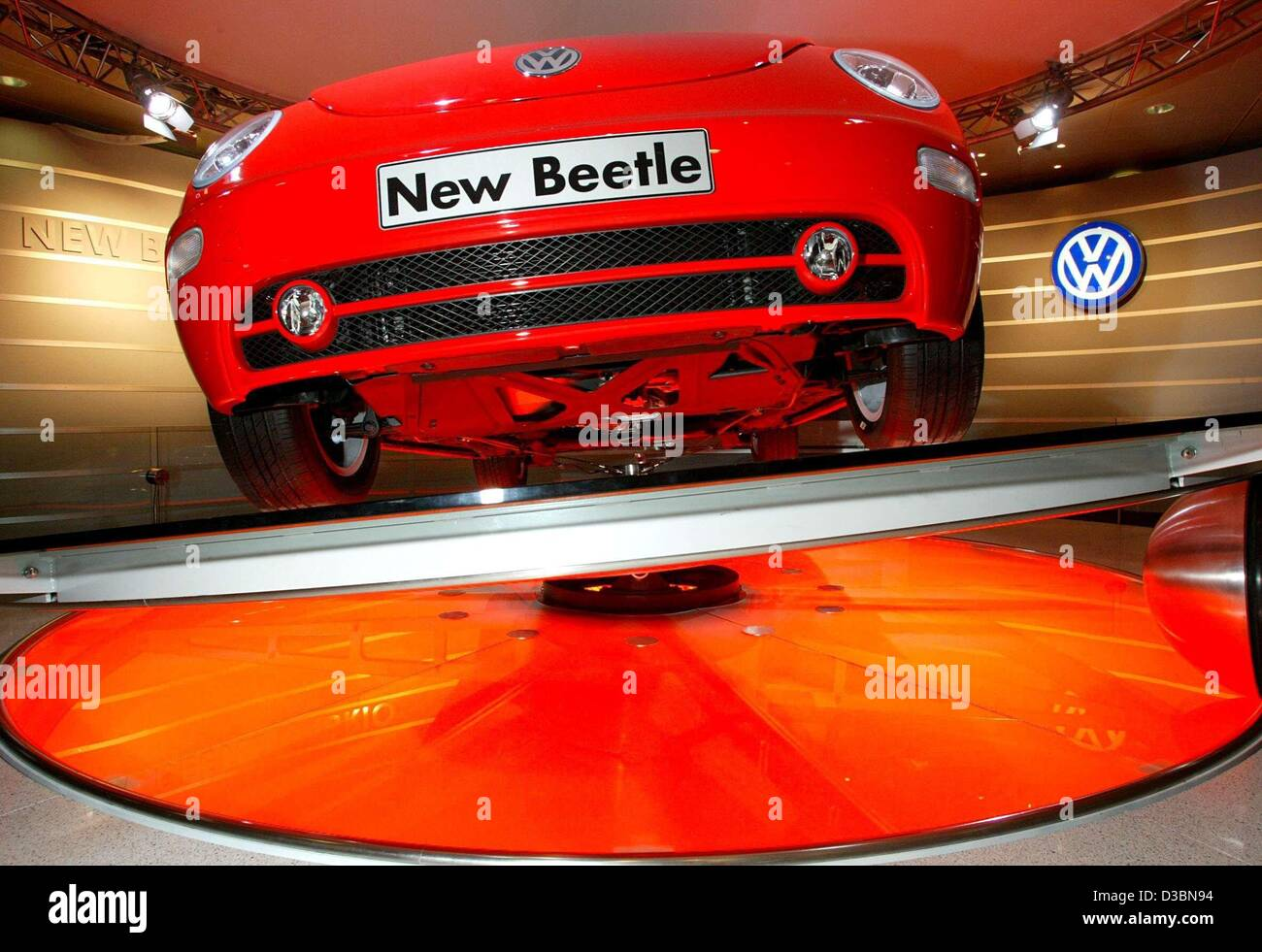 (dpa) - A red VW New Beetle rotates on a disc, at the general meeting of the German Volkswagen (VW) car manufacturers - Stock Image