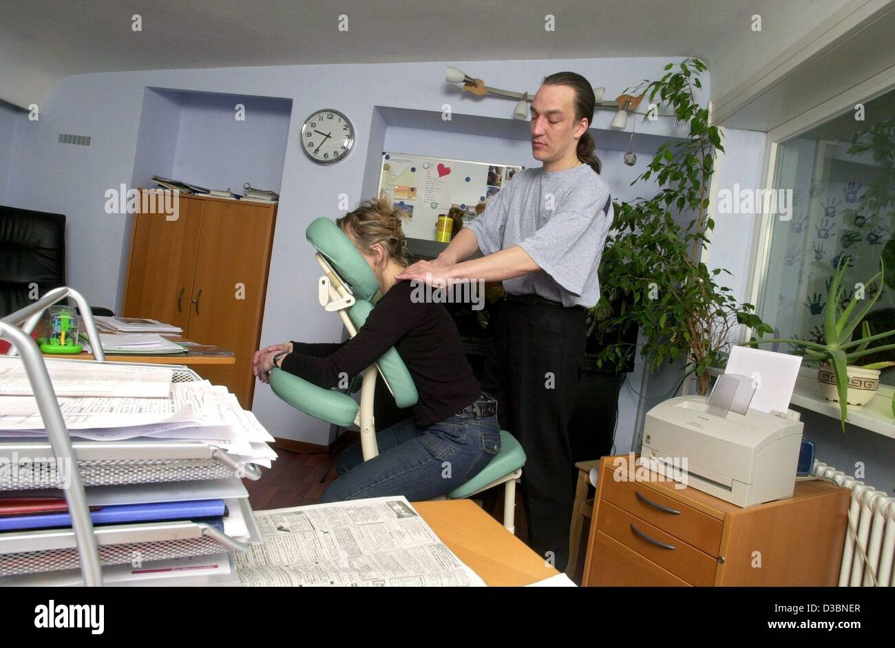 (dpa) - Masseur Cornelius Hinze (R) massages entrepreneur Claudia Urban at her workplace in Stuttgart, Germany, - Stock Image