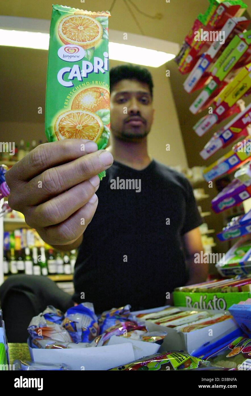 (dpa) - A shop assistant holds a Capri water ice with orange flavour from Langnese into the camera at a kiosk in - Stock Image