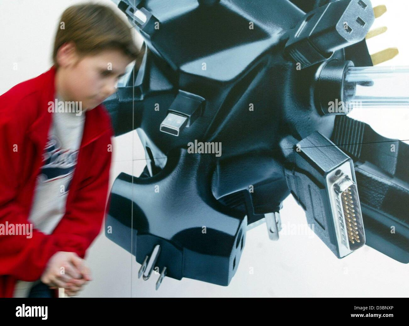 (dpa) - A boy walks past a poster showing oversize computer plugs at the world's largest computer trade fair - Stock Image