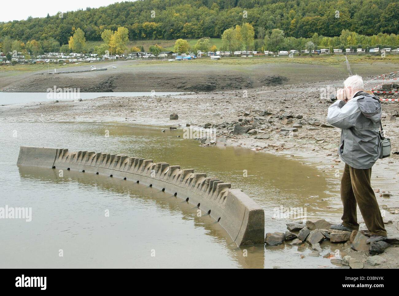 (dpa) - A man takes a photo of the model of the Edersee Dam which was exposed on the bottom of the lake due to the - Stock Image