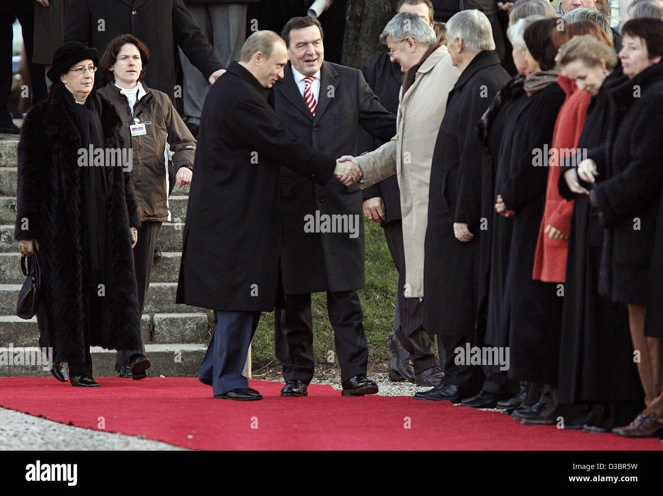 (dpa) - German Chancellor Gerhard Schroeder (C) looks on as Russian President Vladimir Putin (L) shakes hands with - Stock Image