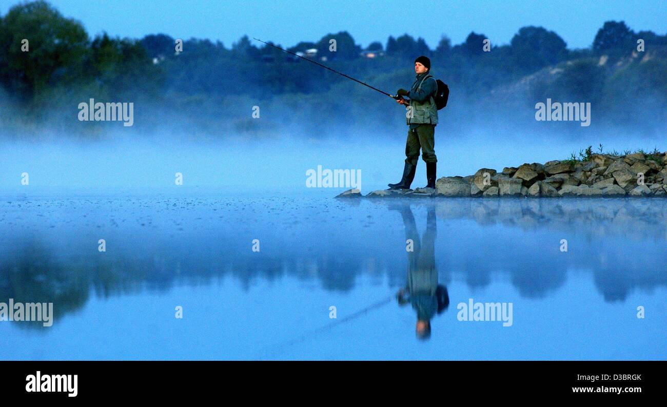(dpa) - Early in the morning a hobby-fisher stands at the foggy river bank of the Oder and waits for a fish to bite - Stock Image