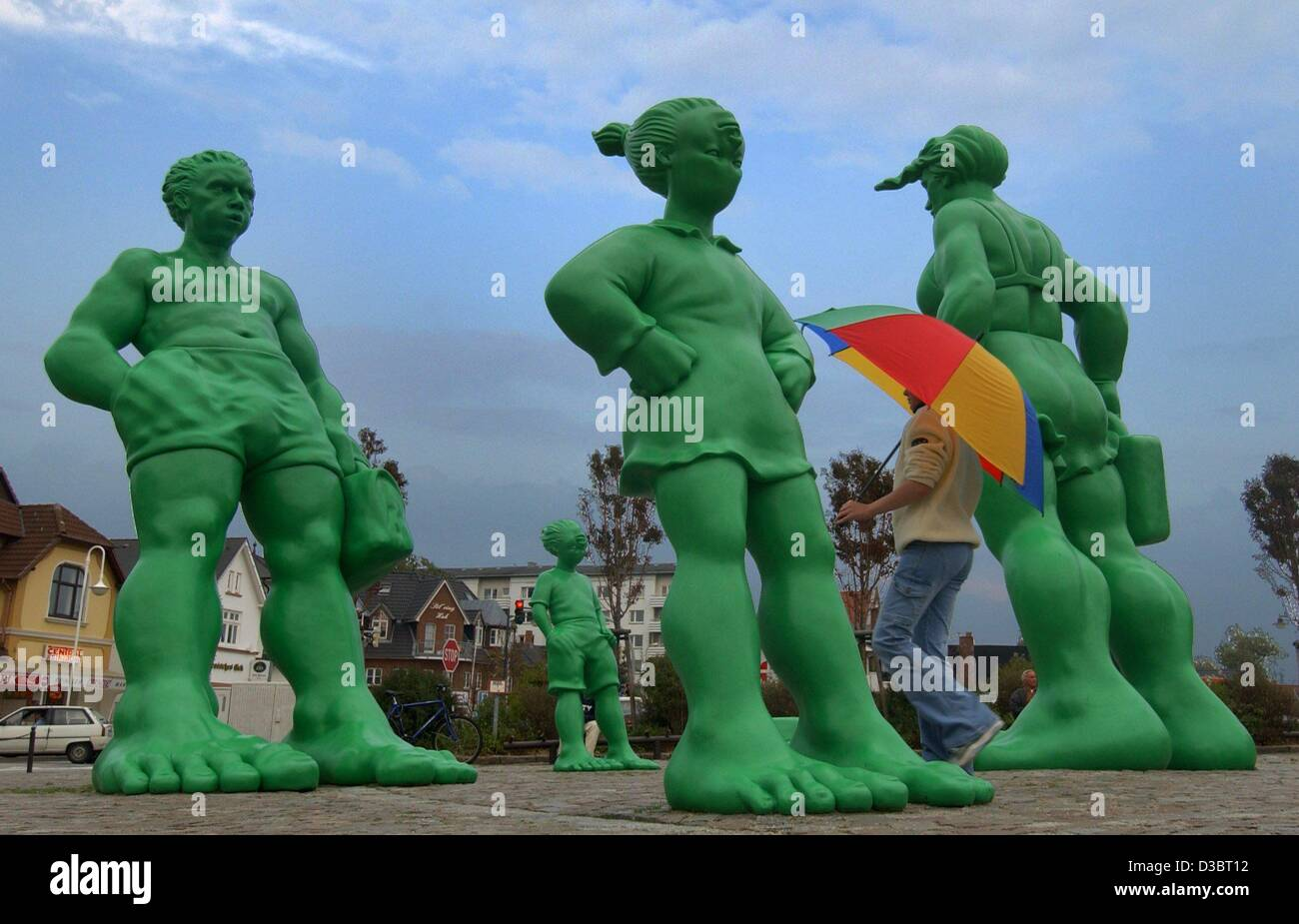 (dpa) - A passer-by walks through the group of skew 'travelling giants' in front of the train station in - Stock Image