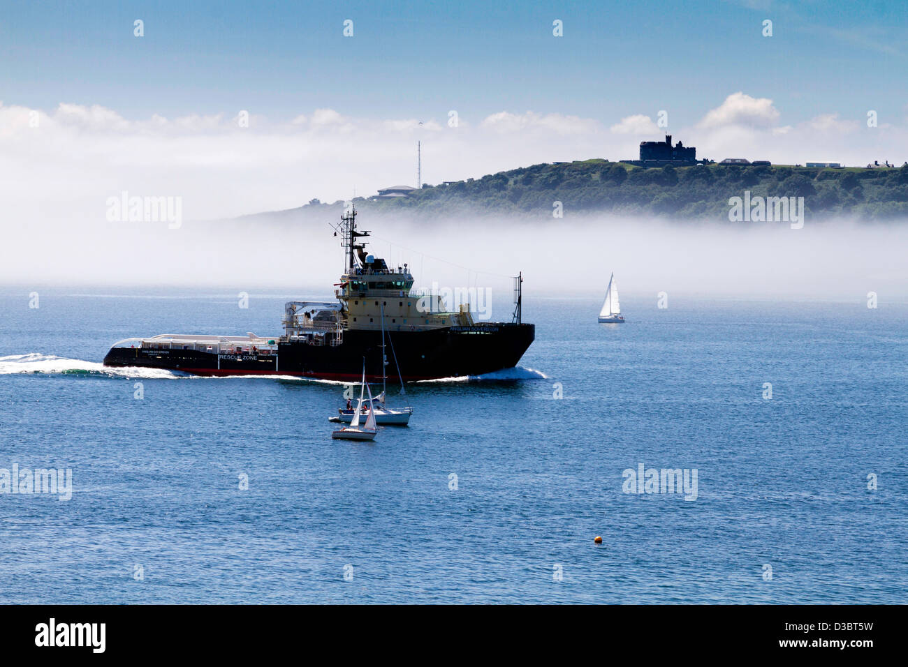 The Anglian Sovereign enters Carrick Roads with a fog bank building on the far side of the estuary - Stock Image