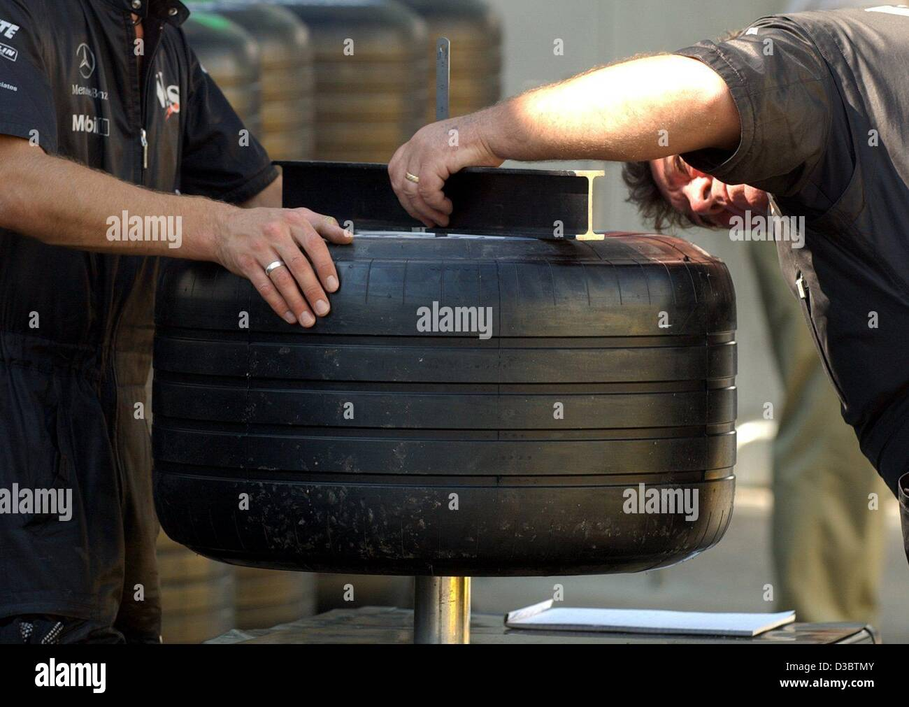 (dpa) - Mechanics of the McLaren-Mercedes team take meticulously the measure of a race tyre, at the formula one - Stock Image