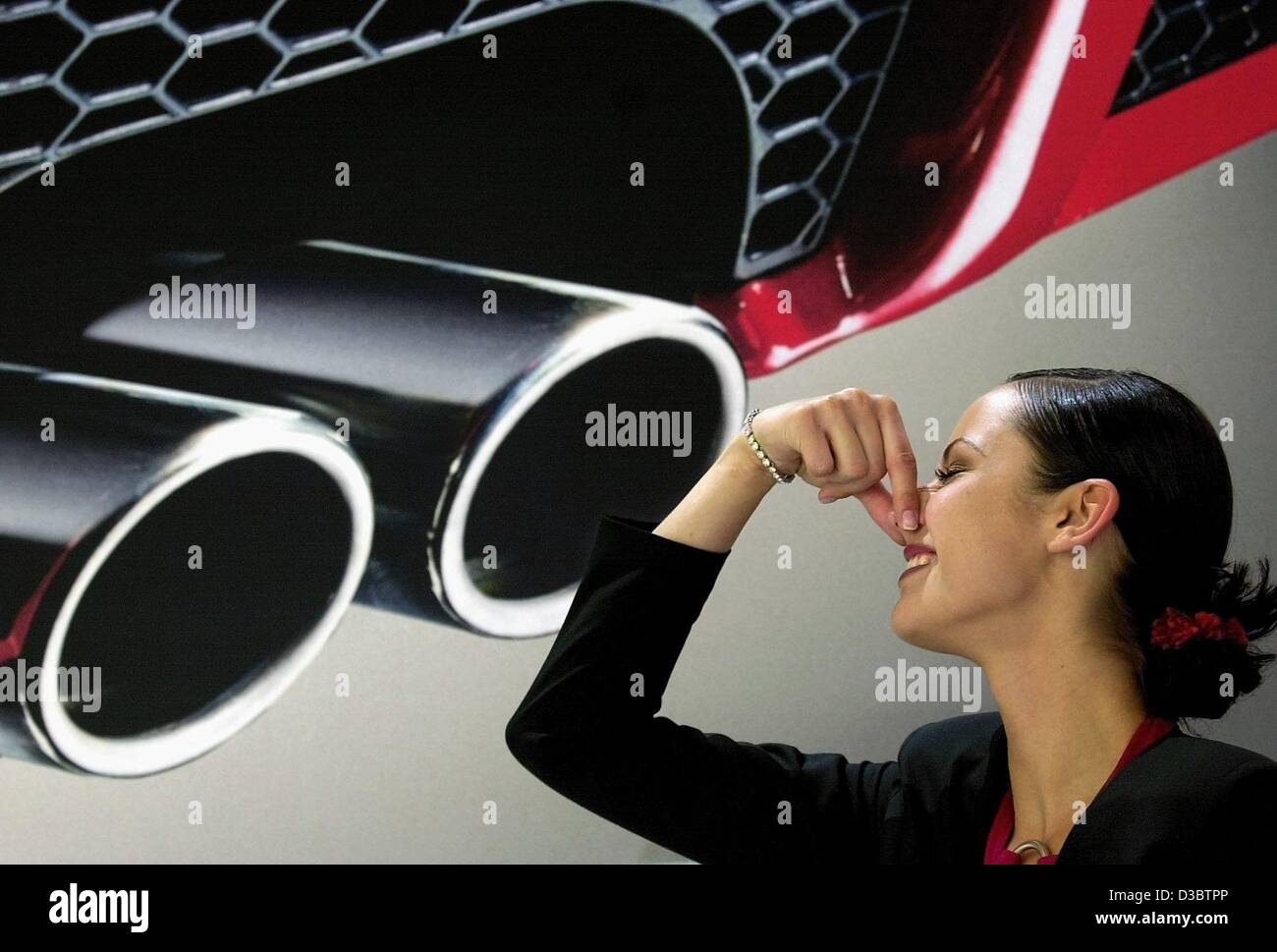 (dpa) - A hostess holds her nose in front of an oversize exhaust pipe of a car, pictured during the 60th International - Stock Image
