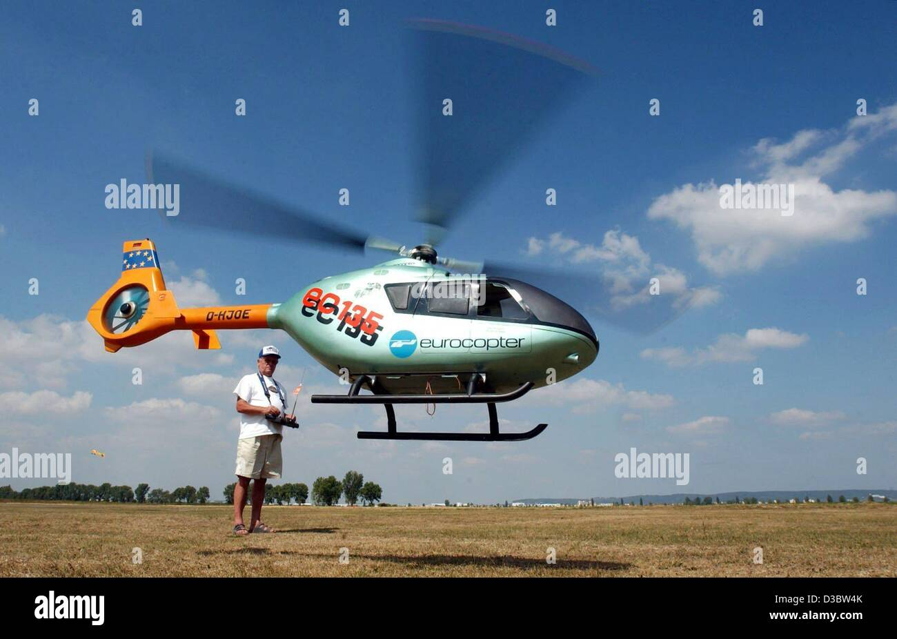 (dpa) - A true-to-scale model of an EC 135 Eurocopter is controlled by a man on the airfield for model aircrafts - Stock Image
