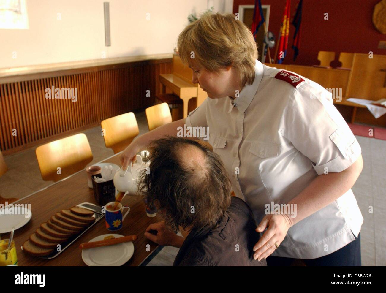 (dpa) - A female Major of the Salvation Army pours cup of tea for a man in need, in Cologne, Germany, 29 July 2003. - Stock Image