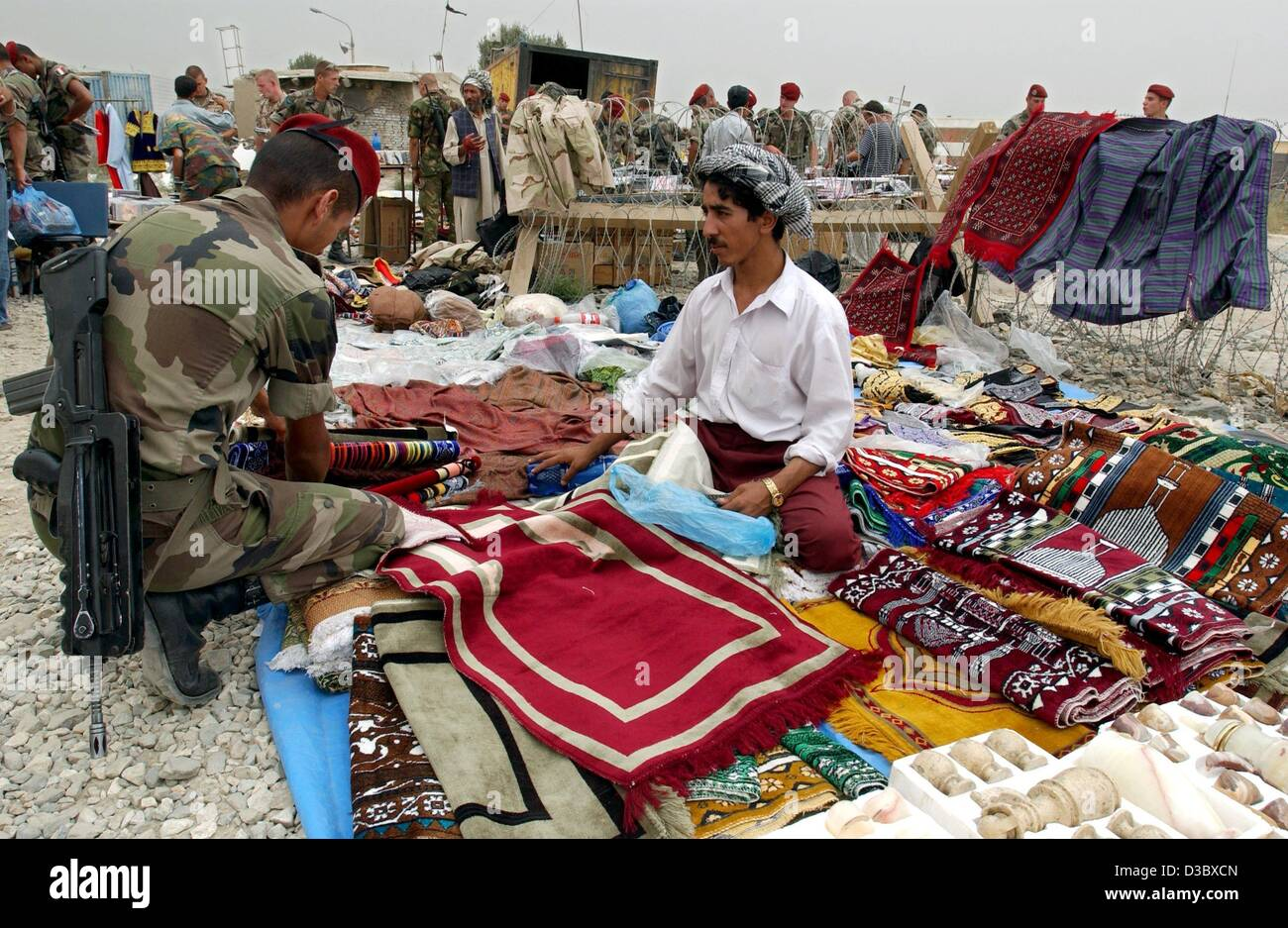 (dpa) - A German soldier looks, in his spare time, through stacks of carpets, textiles and other merchandise at - Stock Image