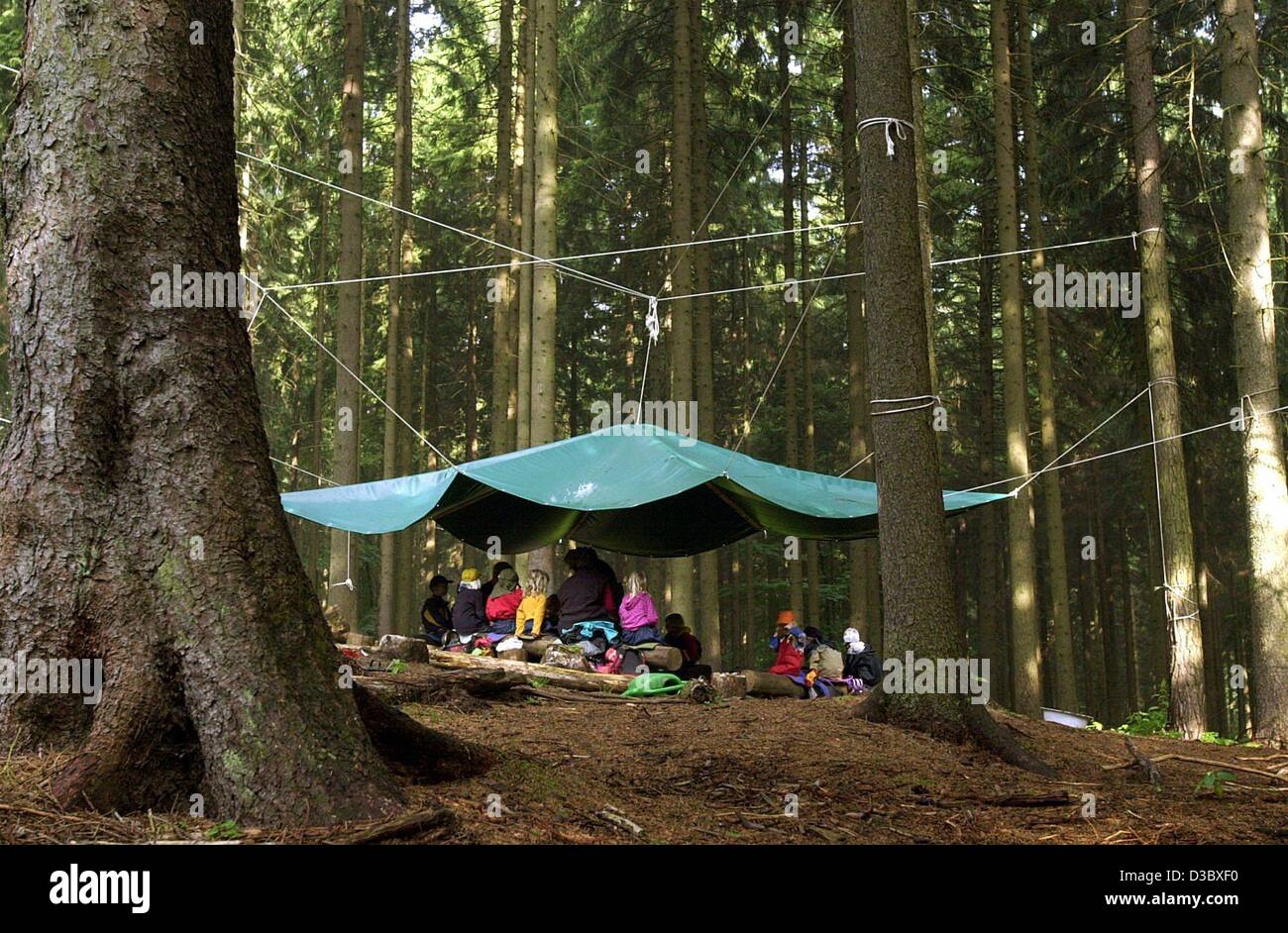 (dpa) - A group of children and their supervisors sit underneath a tent roof in of the forest kindergarden 'Wurzelzwerge' - Stock Image