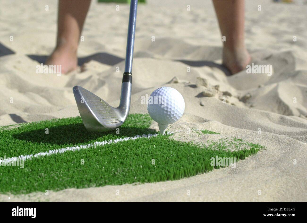 (dpa) - A golfer plays a tee-off on the beach in Ahlbeck on the island Usedom, Germany, 4 August 2003. Behind volleyballers - Stock Image