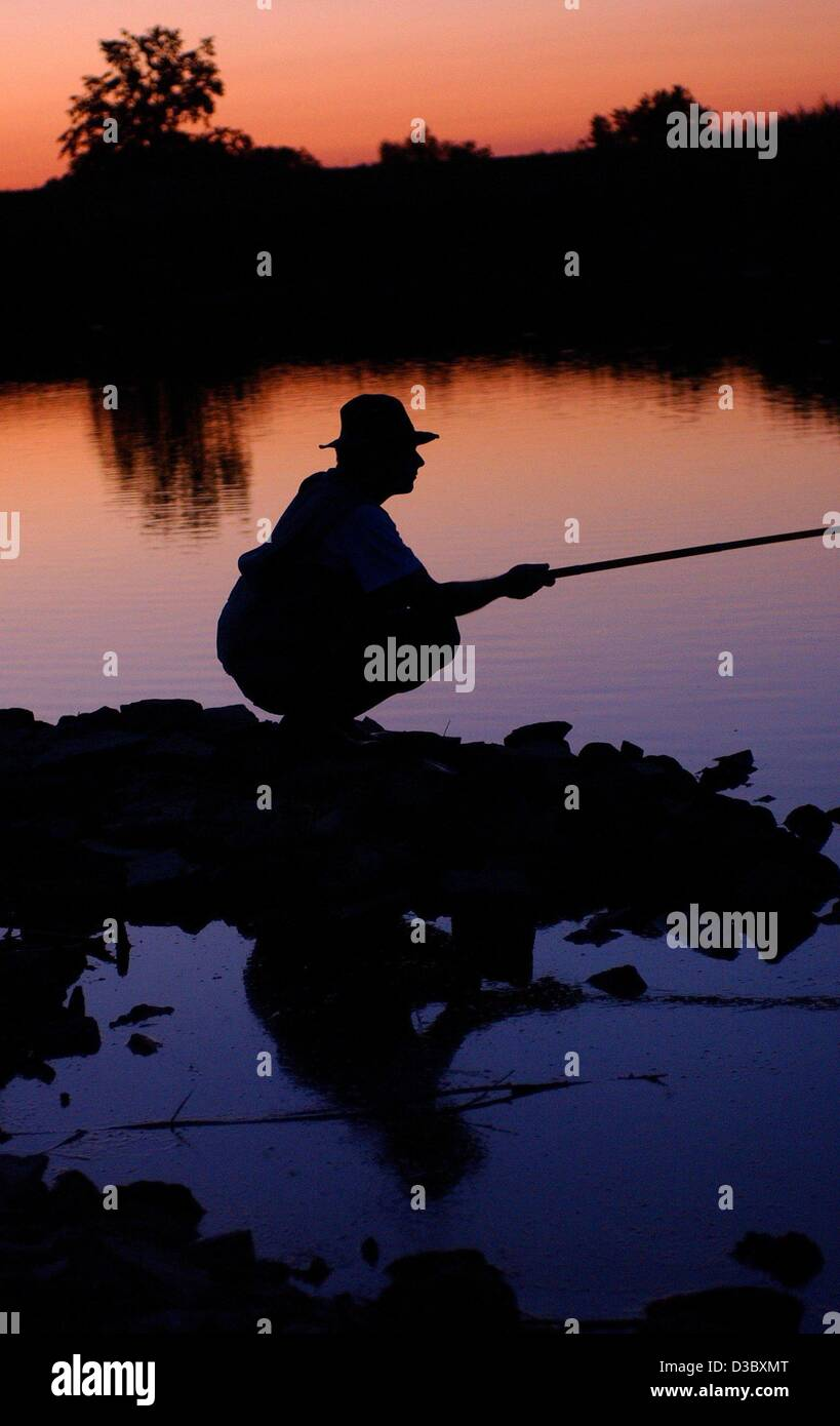 (dpa) - A fisher squats on the river bank waiting for a fish to bite while the sun is setting over the river Oder - Stock Image
