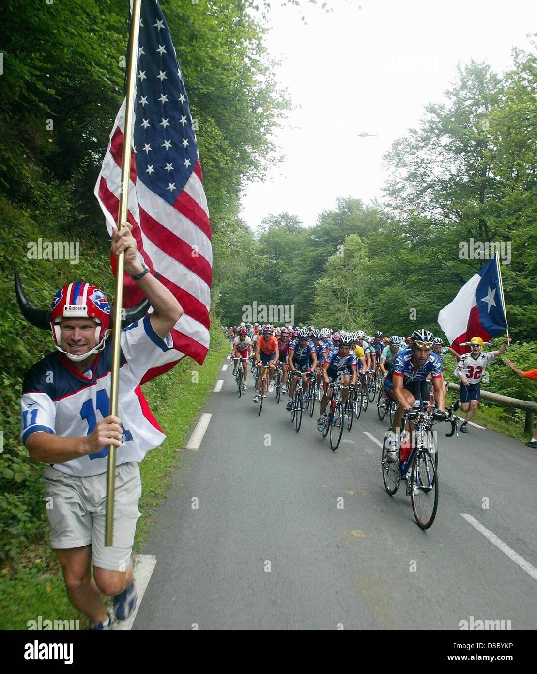 dpa) - Spectators carry US (L) and Texan (R) flags as they run along