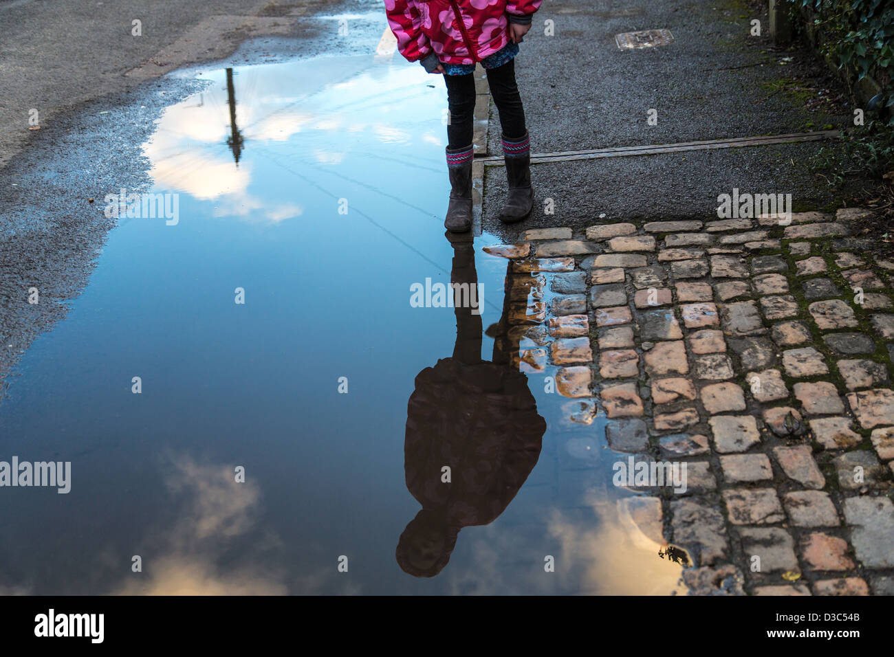 Girl stares at her reflection in a Puddle - Stock Image