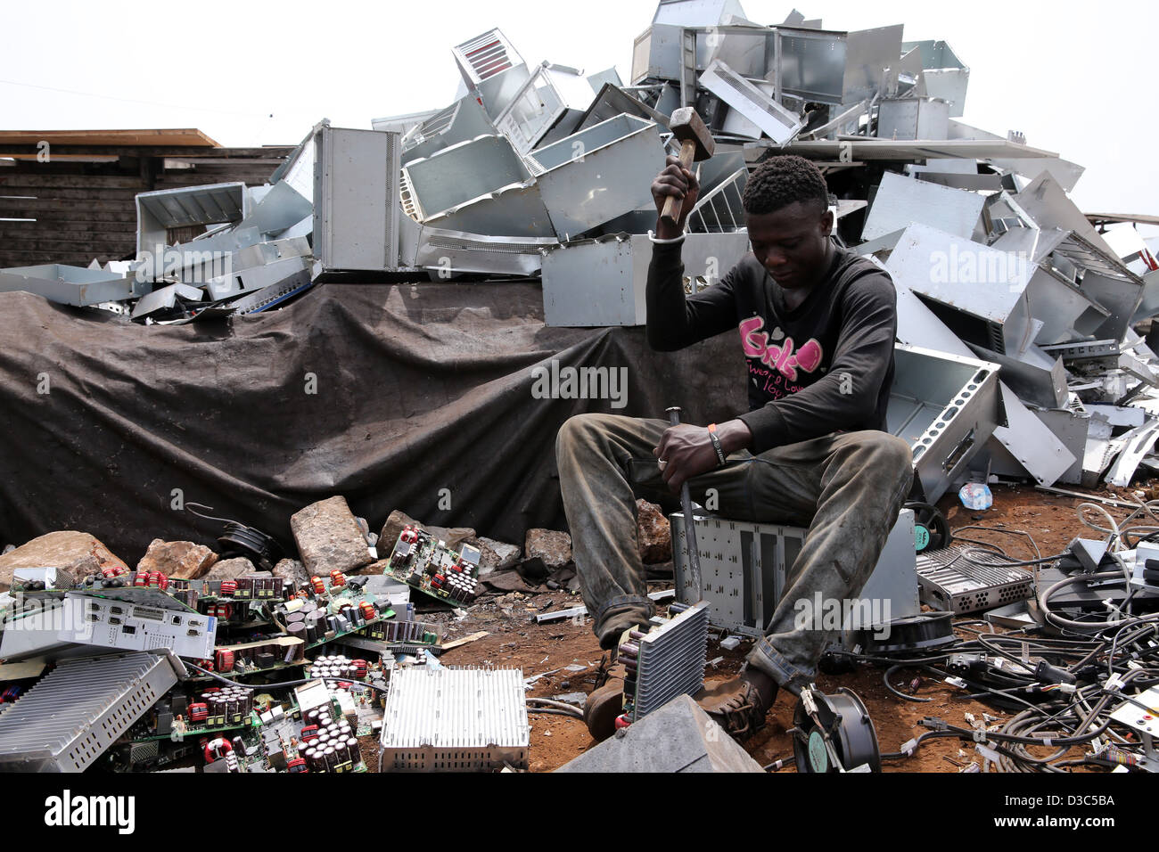 Teenage boys dismantle computer servers and other electronics to recover copper near the Agbogbloshie slum in Accra, - Stock Image