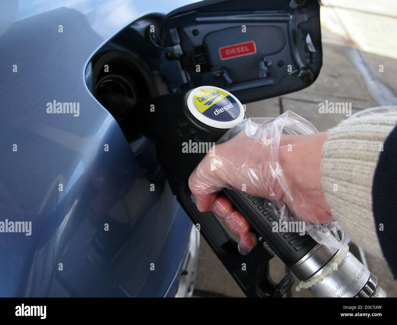 Nozzle filling up car with diesel - Stock Image