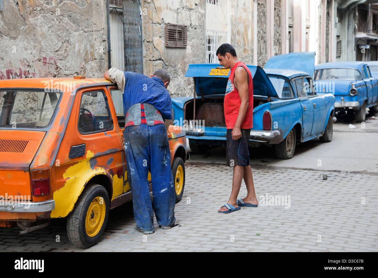 1950s vintage American cars / Yank tank and Cuban car mechanic repairing old car on street in Havana, Cuba, Caribbean - Stock Image