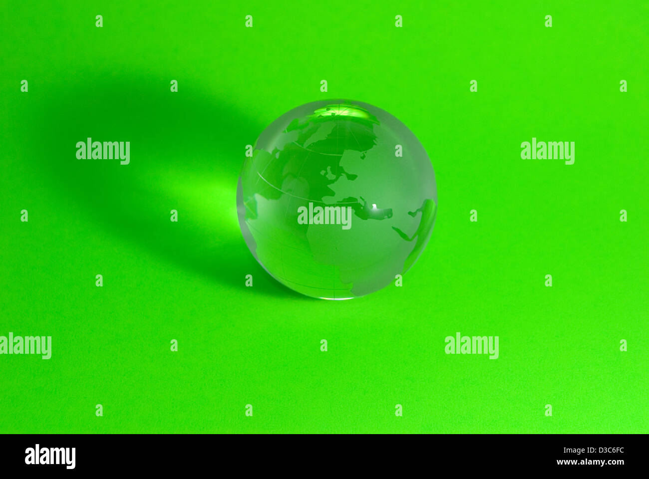 Glass earth globe or sphere on green background - Stock Image