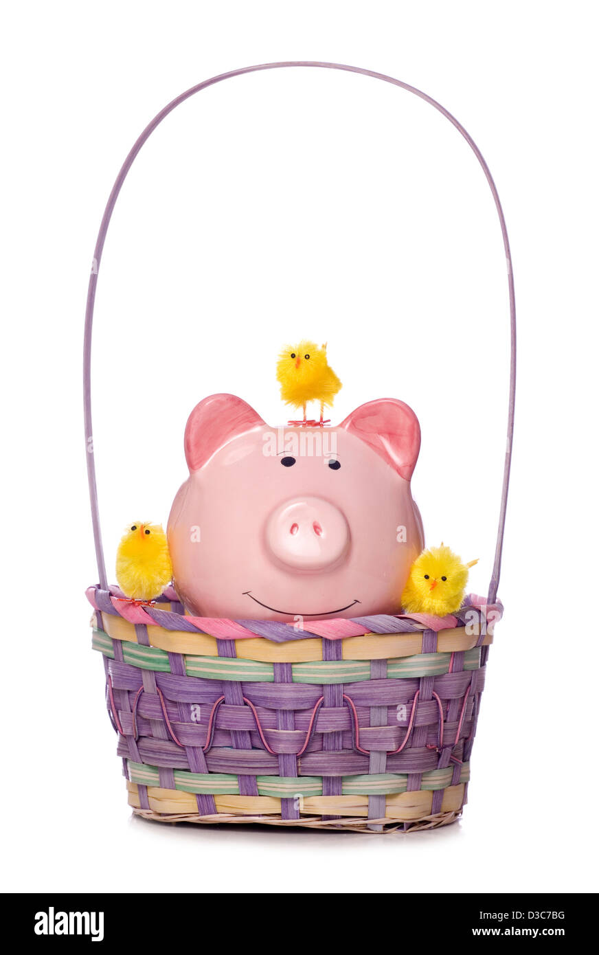 easter chicks and piggy bank in a basket studio cut out Stock Photo