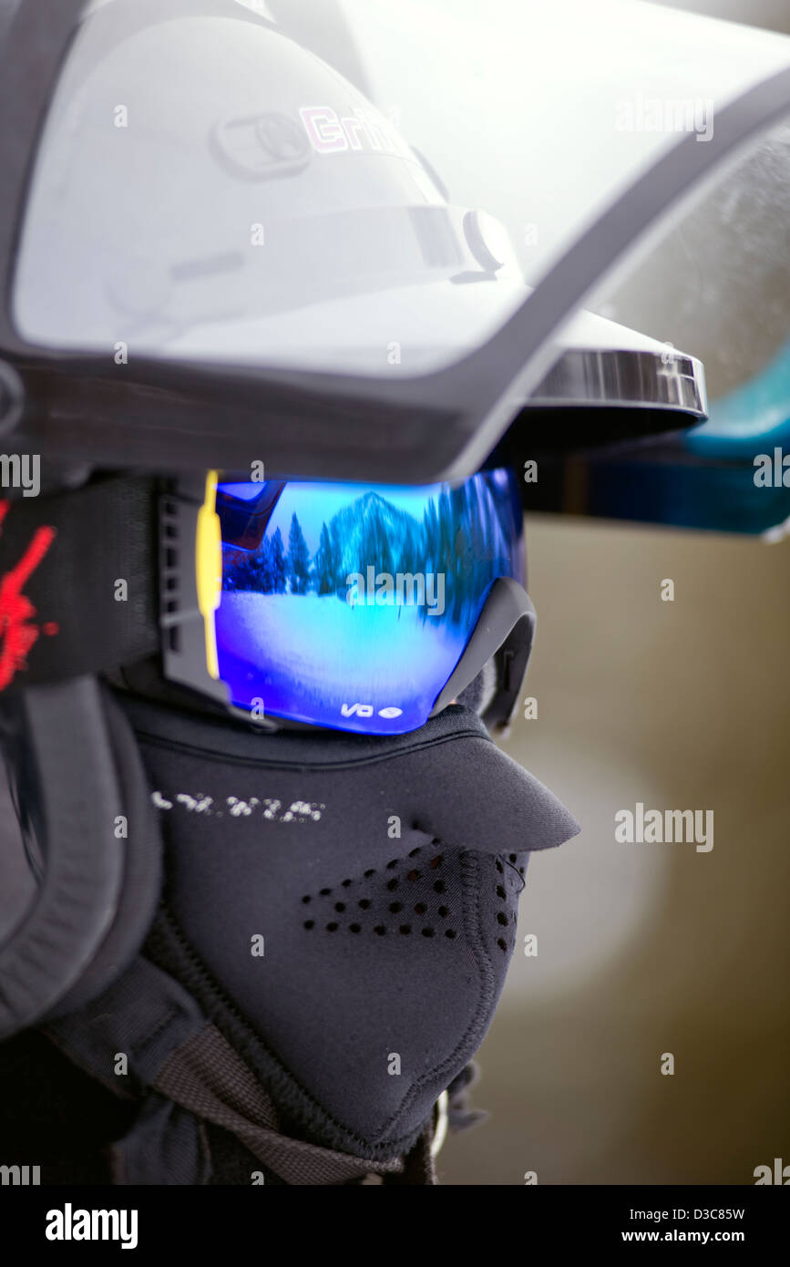 Man wearing protective headgear, face mask and reflective goggles while riding a snowmobile - Stock Image