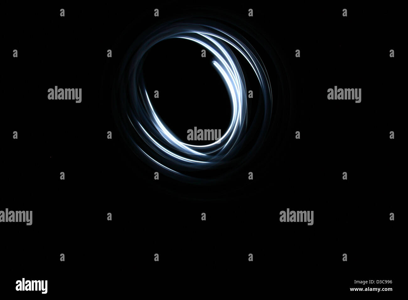 painted circle with light in shape of black hole - Stock Image