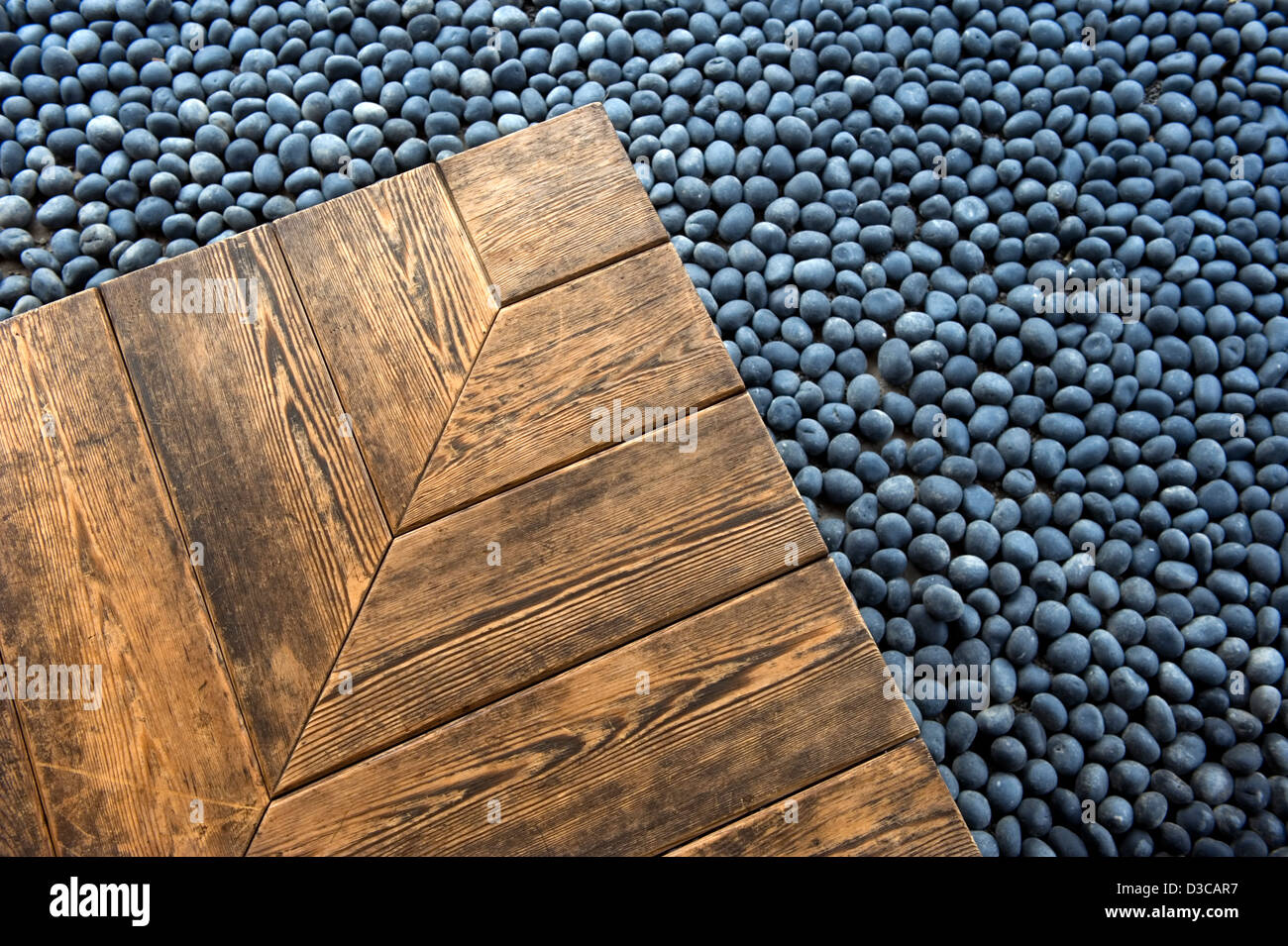 Corner of warm grainy wood veranda deck contrasts with background of smooth round blue river rock in Japanese garden - Stock Image