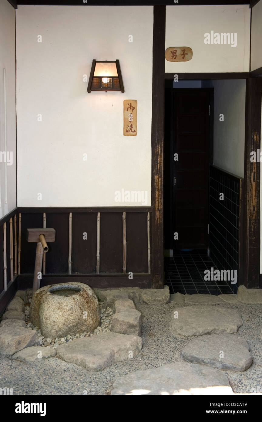 Entrance to Japanese style men's public restroom, or 'honorable hand wash,' as sign says, with tsukubai - Stock Image