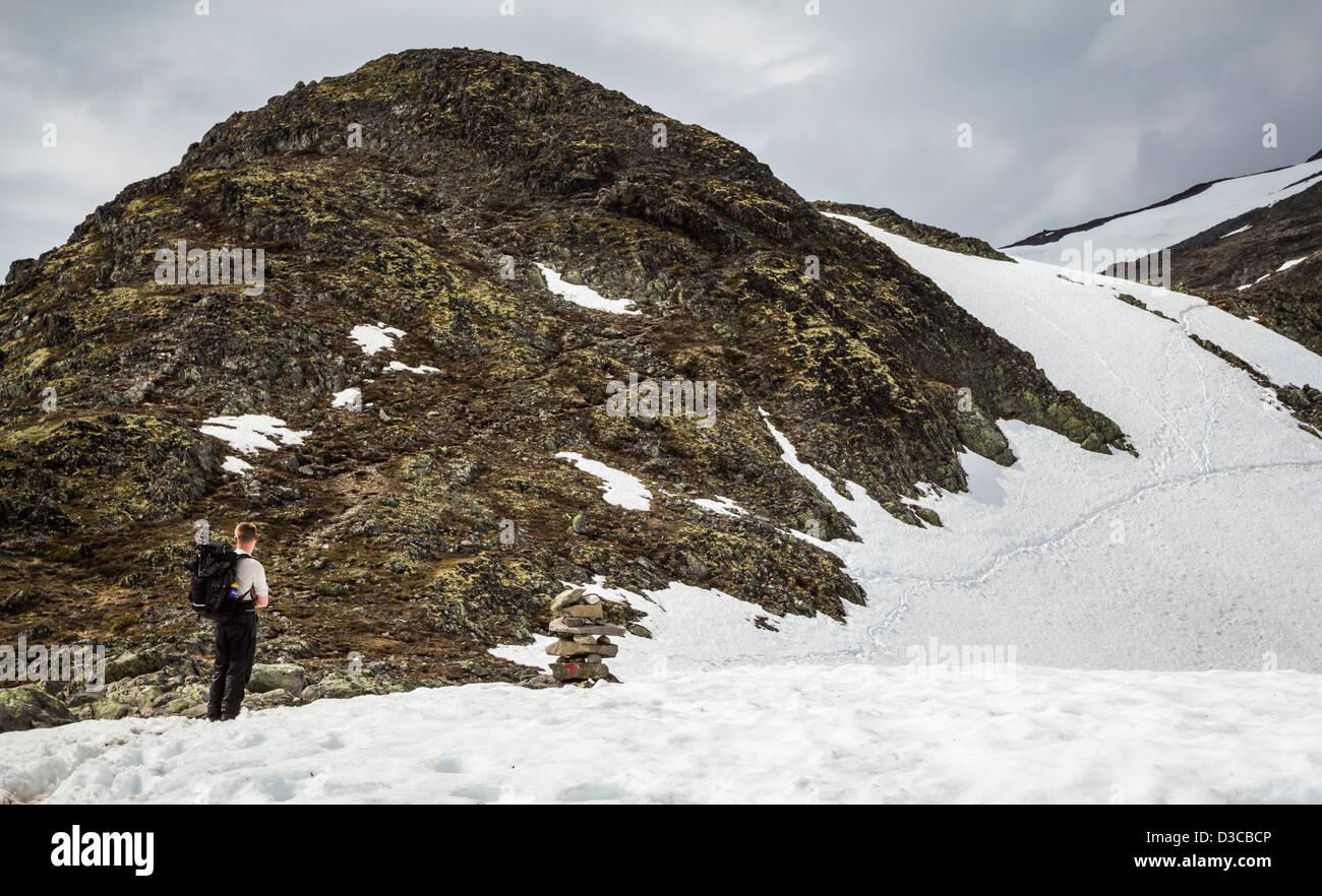 Hiker looking at Mountain Path in Snow, Besseggen, Jotunheimen, Norway - Stock Image