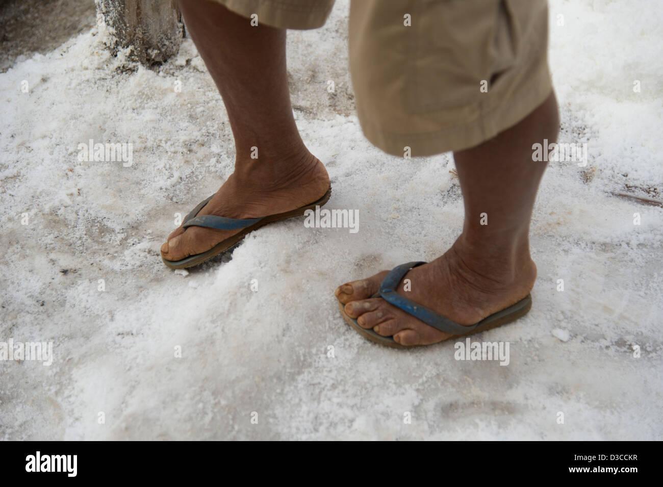 452e6bc37666bd A man wearing flip-flops stands on a pile of salt near Savannakhet in Laos