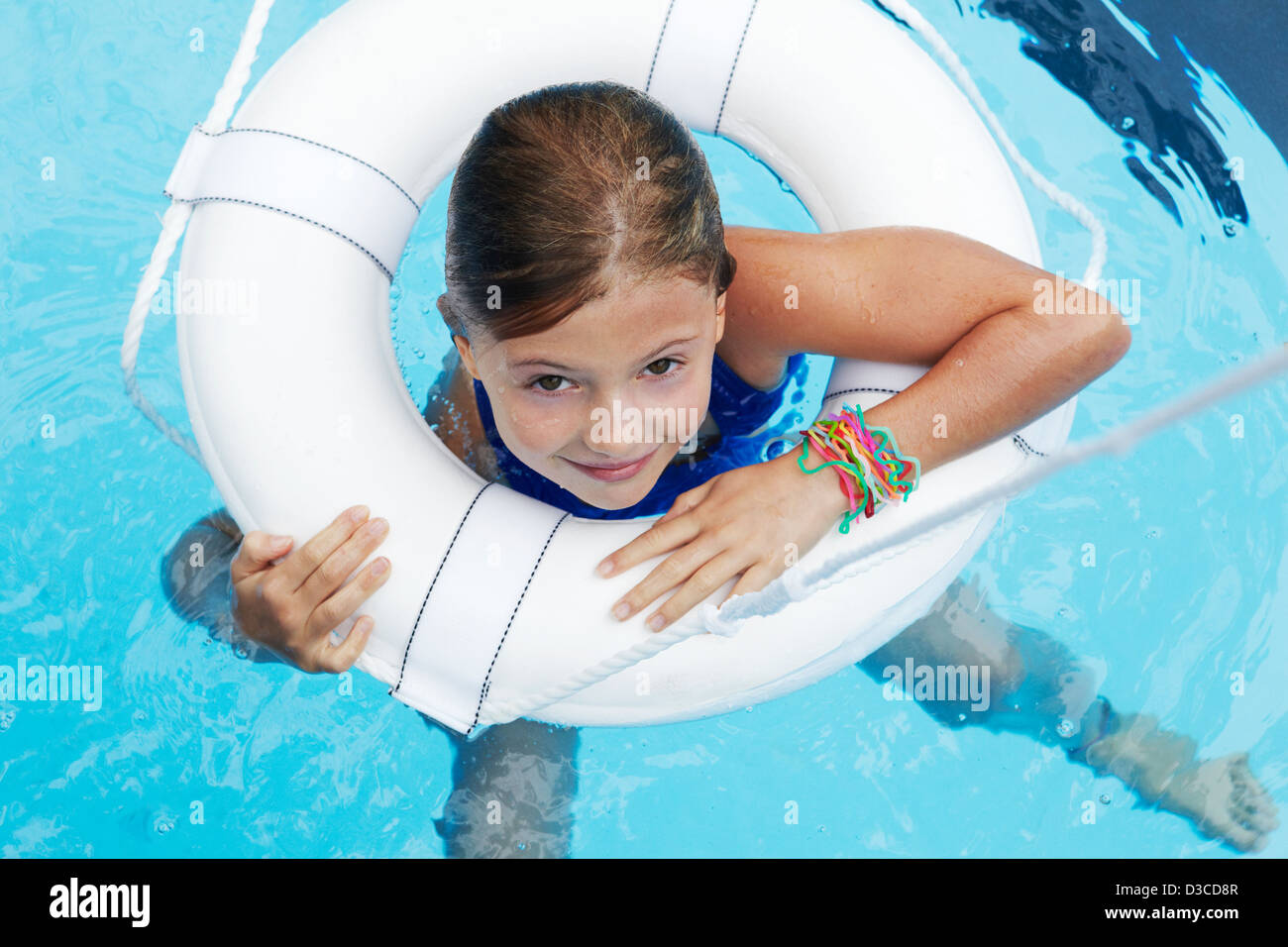 7 year old girl swimming in pool with life preserver - Stock Image