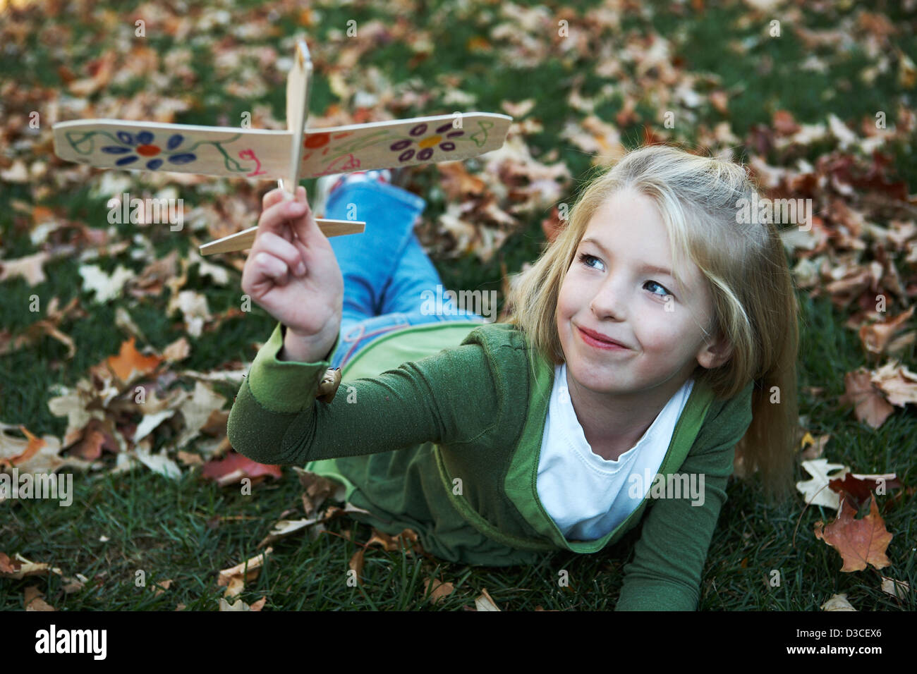 Eight year old girl playing with hand decorated toy glider plane. - Stock Image