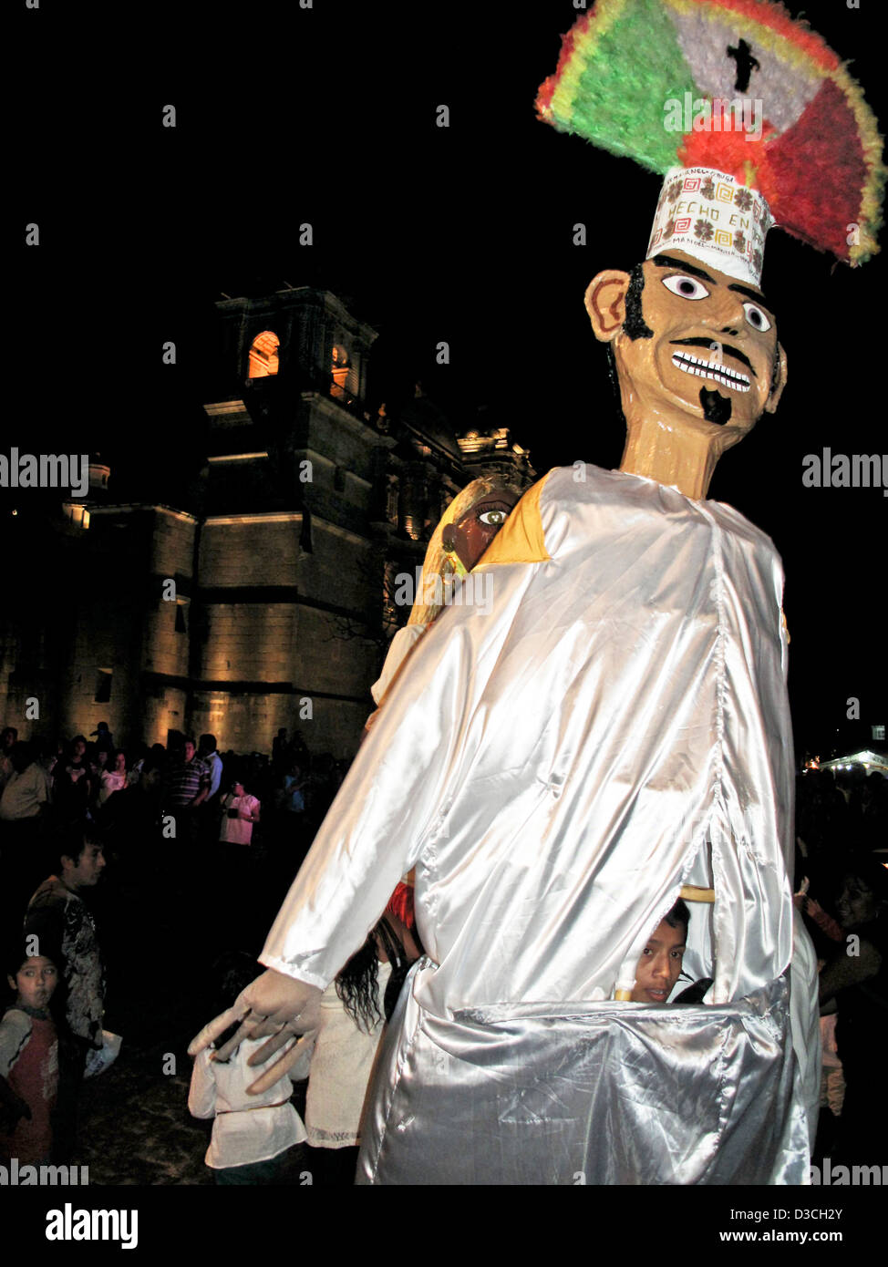 giant puppet with papier mache head & feathered headdress in front of Oaxaca Cathedral with face of teen boy - Stock Image