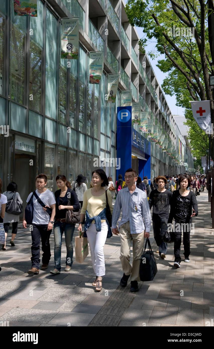 Shoppers strolling past Omotesando Hills shopping mall along Omotesando-dori Street in the upscale Shibuya ward - Stock Image