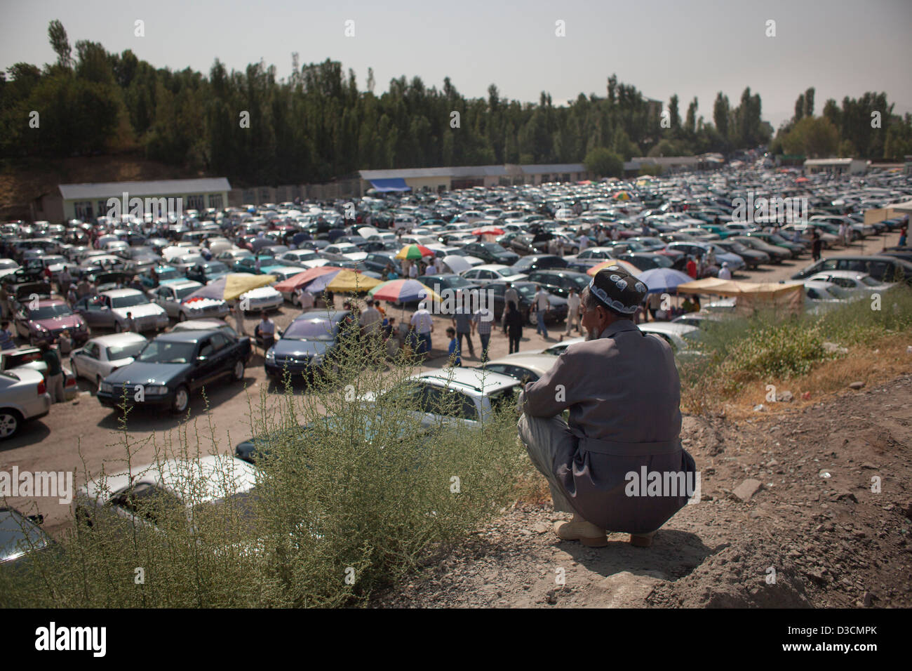 An old man sits on a hill above a 2nd hand car bazaar in Dushanbe, Tajikistan - Stock Image