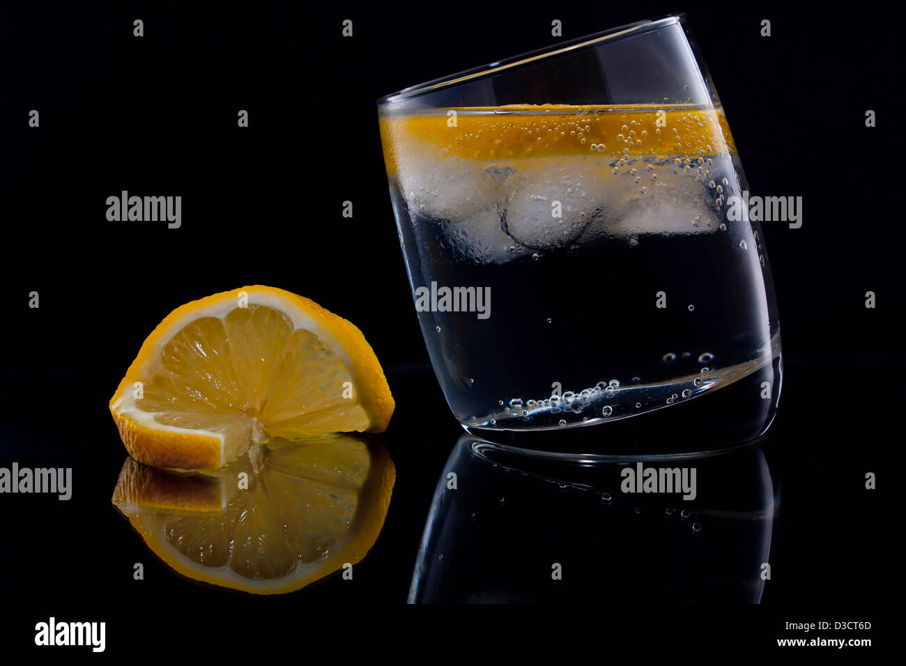 Gin and tonic or vodka and tonic with a slice of lemon over black - Stock Image