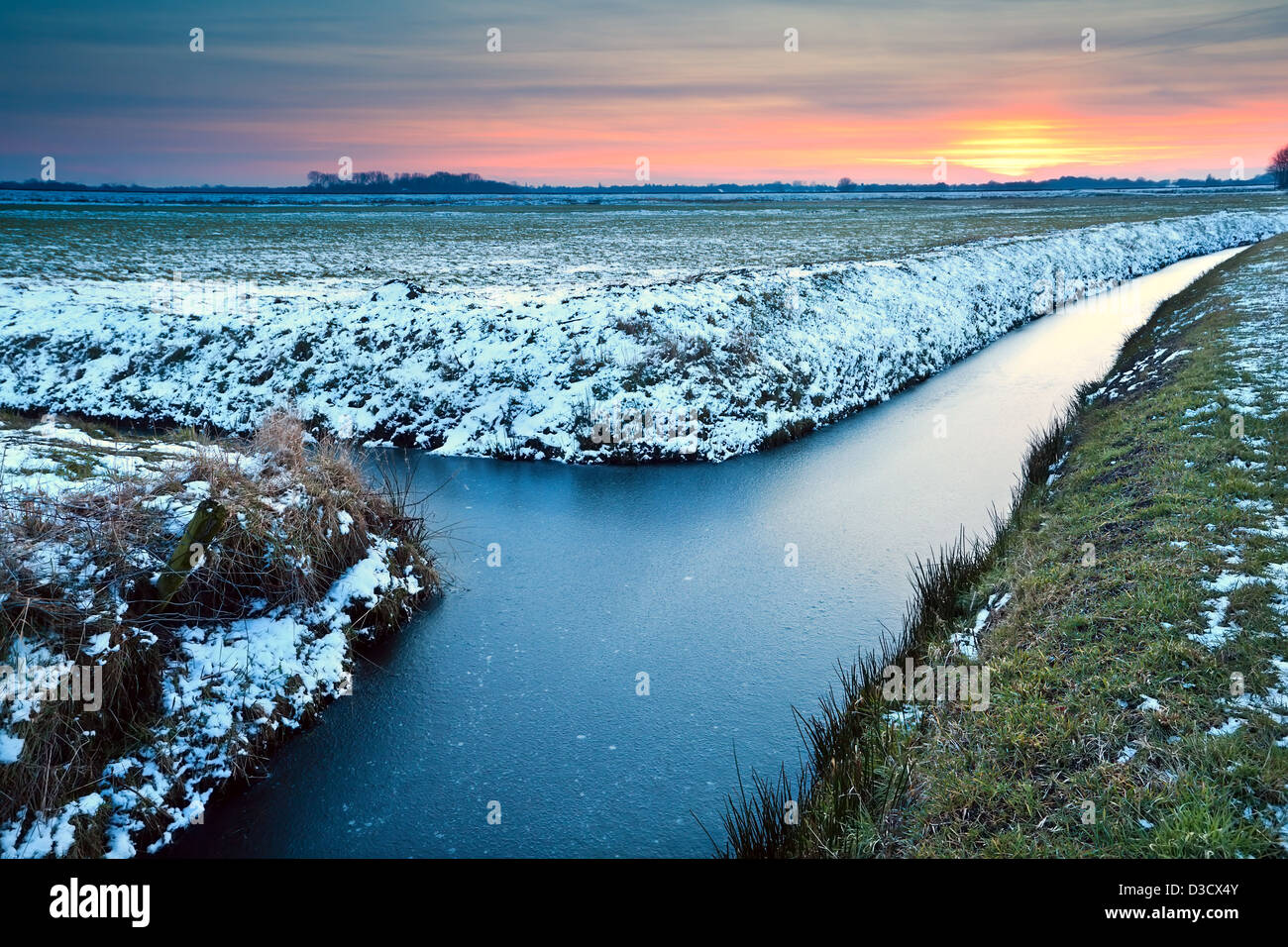 sunset over winter meadows and frozen canals in Netherlands - Stock Image