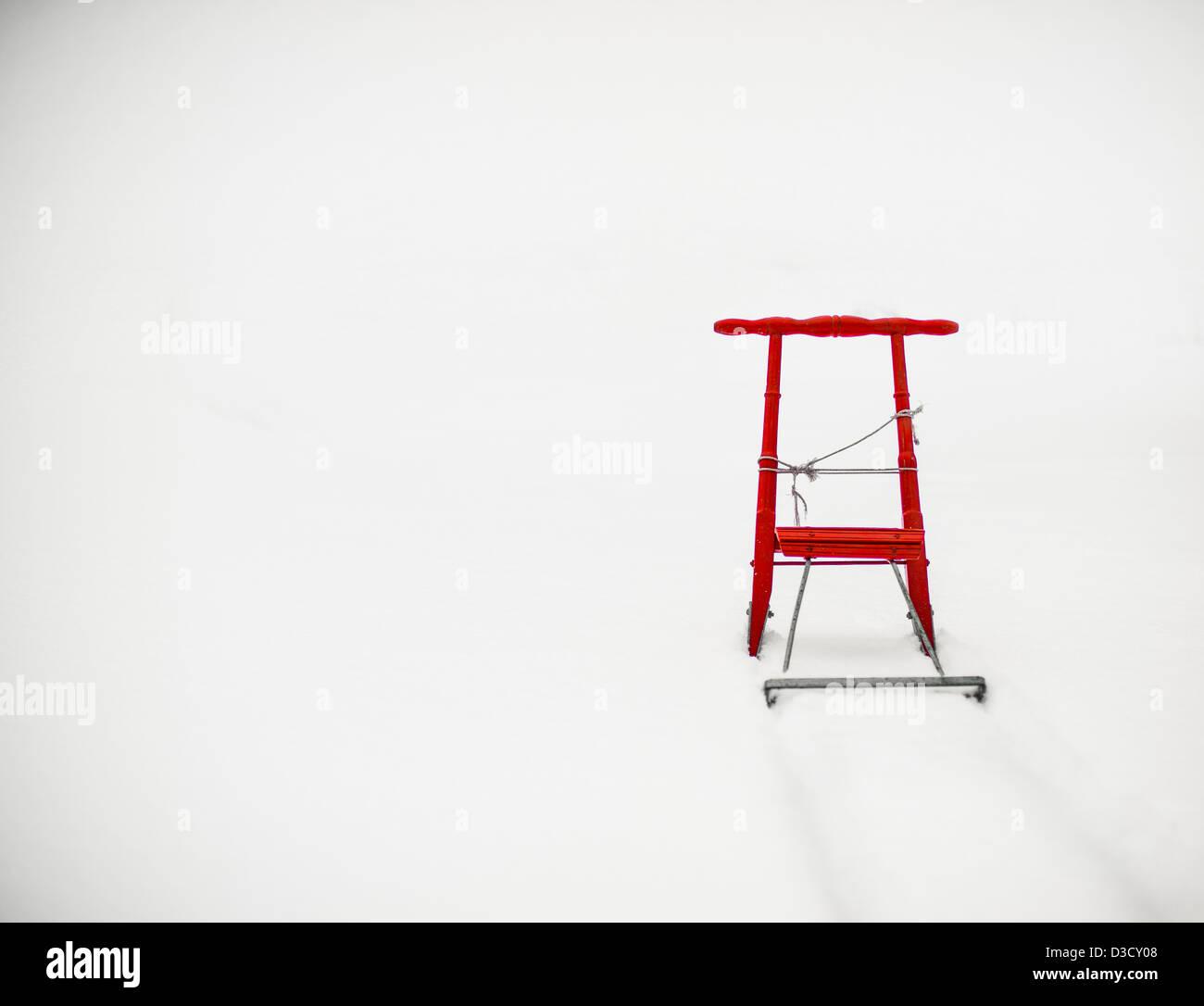 Orange children's sleigh in the snow - Stock Image