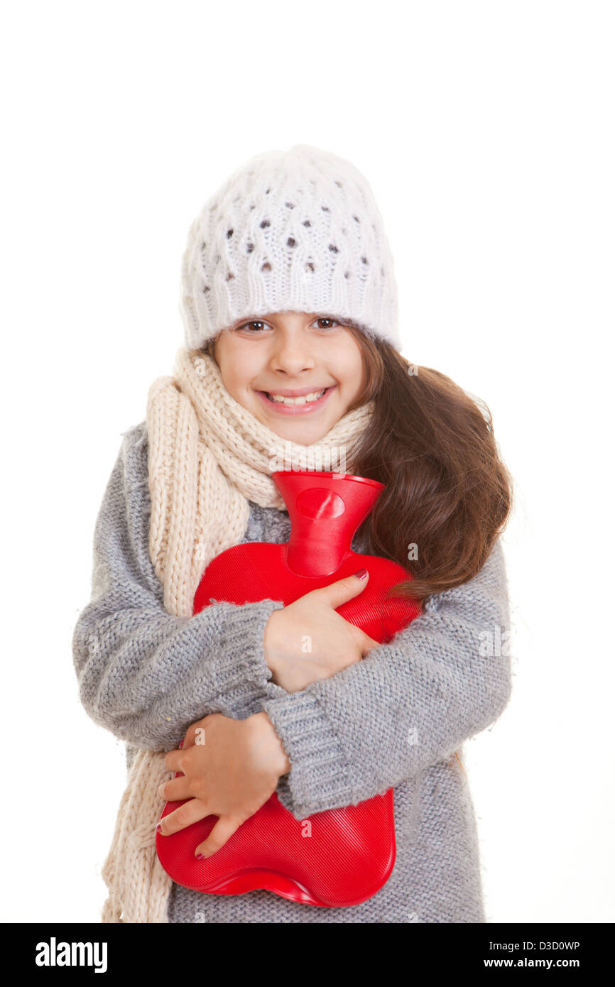 winter child hugging hot water bottle for warmth - Stock Image
