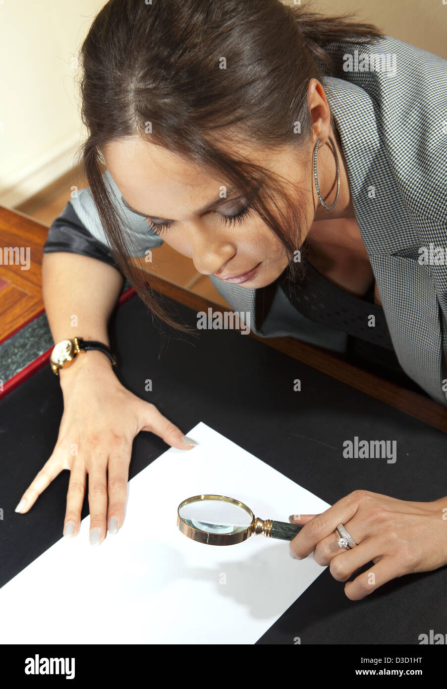 business woman looks on one document by magnifying glass - Stock Image