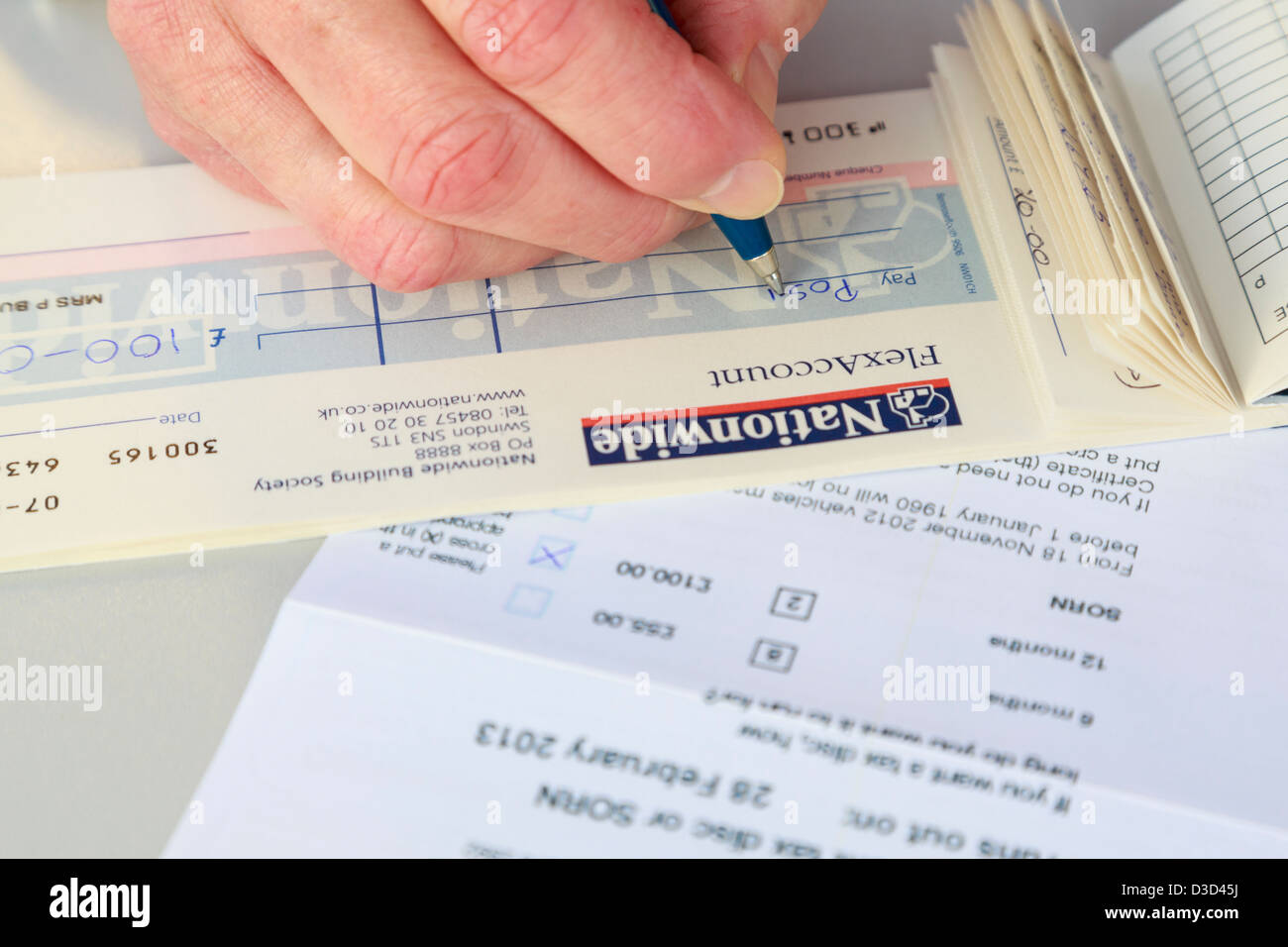 Female person writing a Nationwide cheque to pay for 12 months car tax renewal at the Post Office. England UK Britain - Stock Image