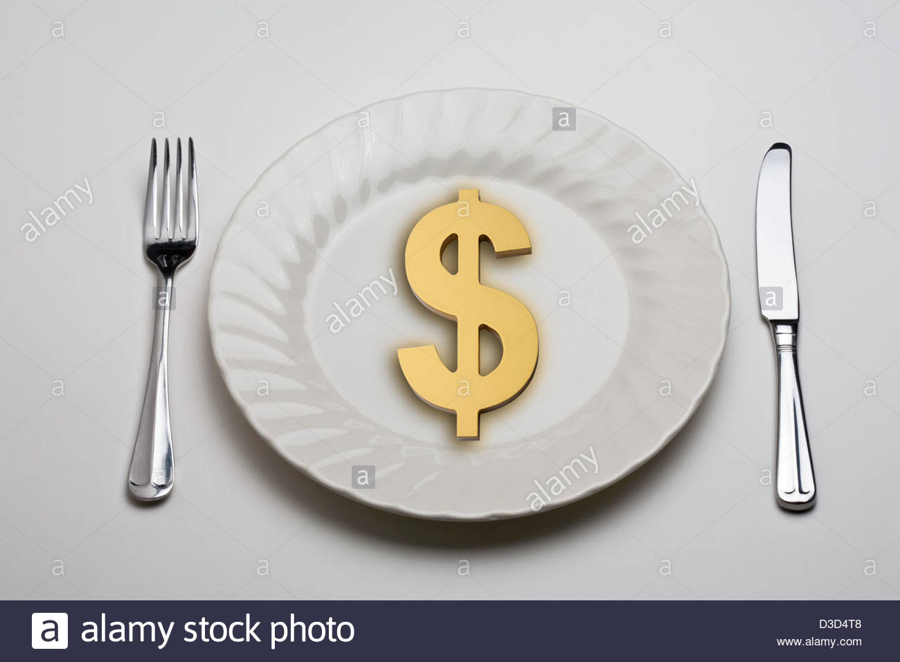 Golden dollar symbol on a white dinner plate with a knife and fork. - Stock Image