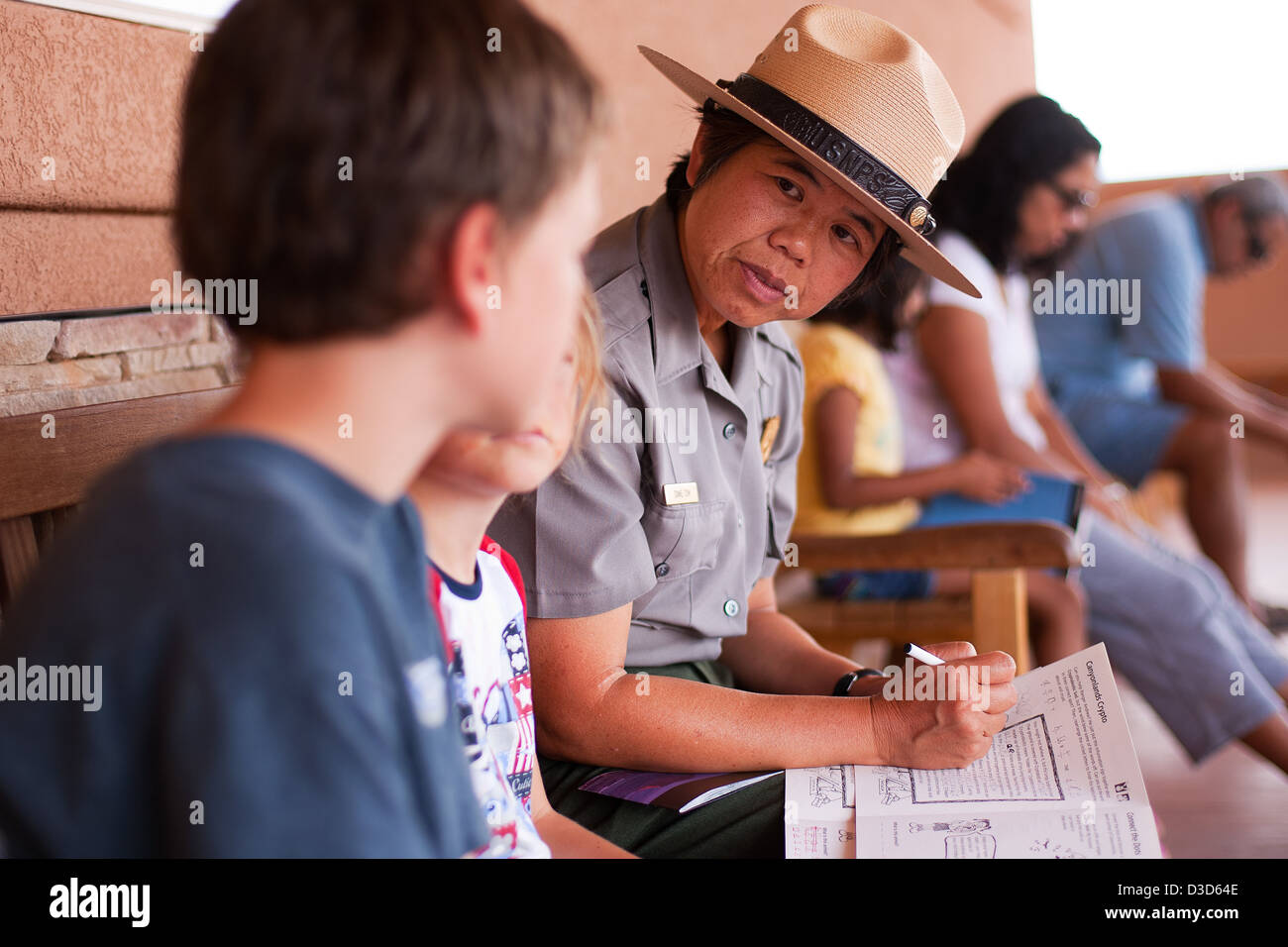 Diane Tom talks with a junior ranger. - Stock Image