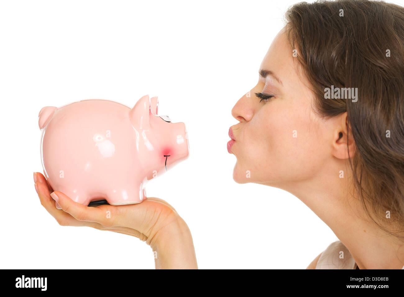 Closeup on young woman kissing piggy bank - Stock Image